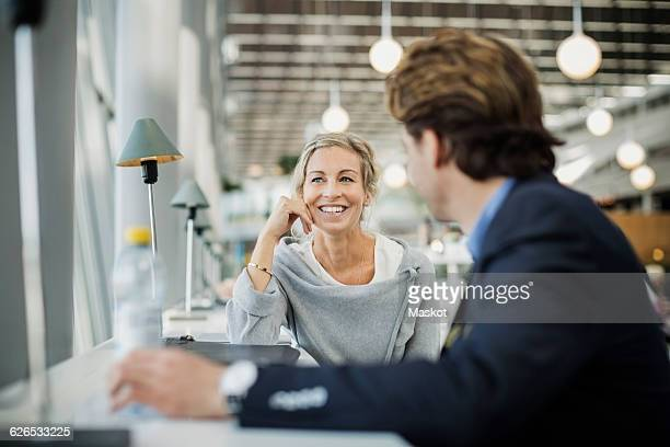 Happy businesswoman talking to colleague at airport cafe
