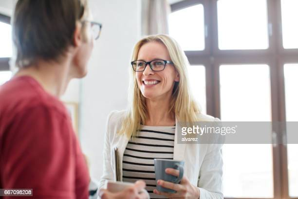 Happy businesswoman talking to colleague in office