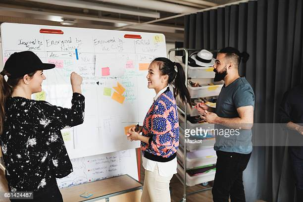 Happy businesswoman talking to colleagues in creative office