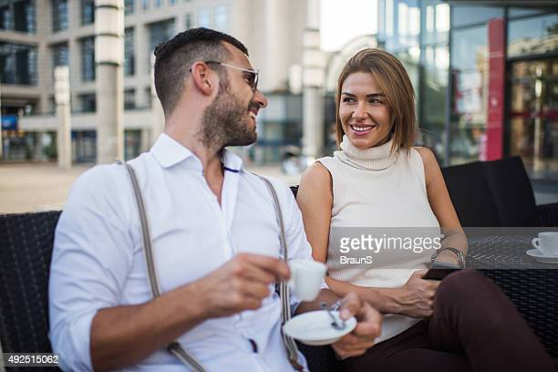 Happy businesswoman talking to her male colleague in a cafe.