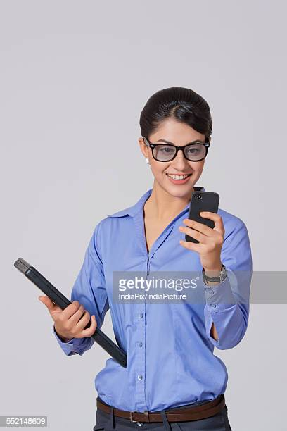 Happy businesswoman using mobile phone while holding laptop against gray background