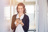 Beautiful mature businesswoman writing a text on smart phone. Smiling woman feeling happy on reading a message on smartphone. Relaxed woman checking email and typing on cellphone at office.