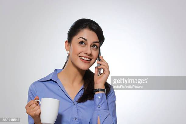 Happy businesswoman with coffee mug answering phone over gray background