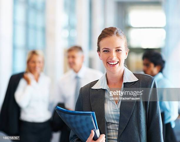 Happy businesswoman with colleagues in the background