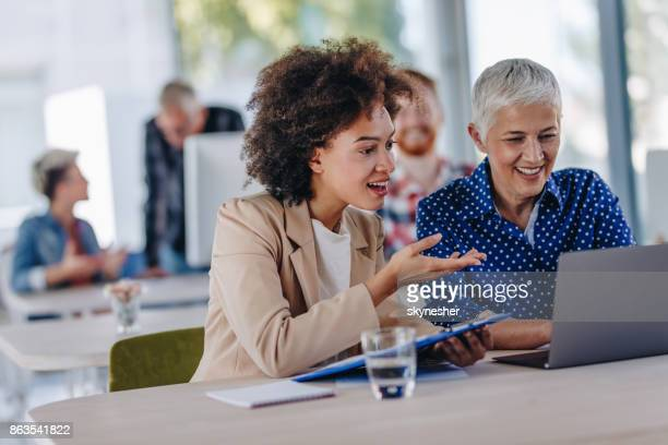 Happy businesswomen cooperating while working on computer at corporate office.