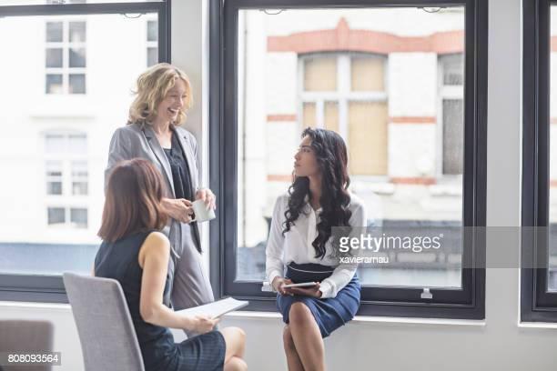 幸せなビジネスウーマンにオフィスの窓際で議論