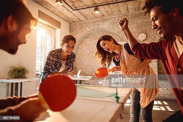 Heureux femmes d'affaires jouant tennis de table contre les hommes d'affaires dans une ambiance décontractée au bureau.