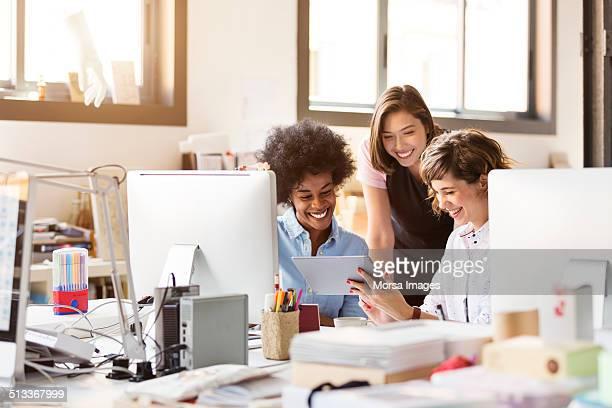 Happy businesswomen using digital tablet in office