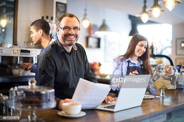 happy cafe owner paying his bills online