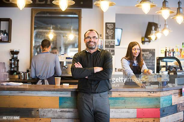happy cafe owner poses to camera