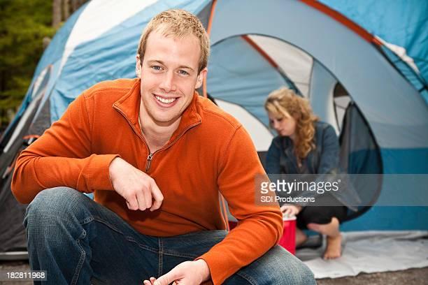 ハッピーキャンパーひざまずく外彼のテントでのキャンプ場