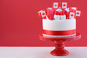 Happy Canada Day celebration cake with flags, marshmallow and candy decorations on a red cake stand on a white table against a red  background.Happy Canada Day celebration cake with flags, marshmallow