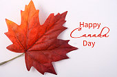 Happy Canada Day symbolic maple leaf on a white wood table with copy space and sample text.