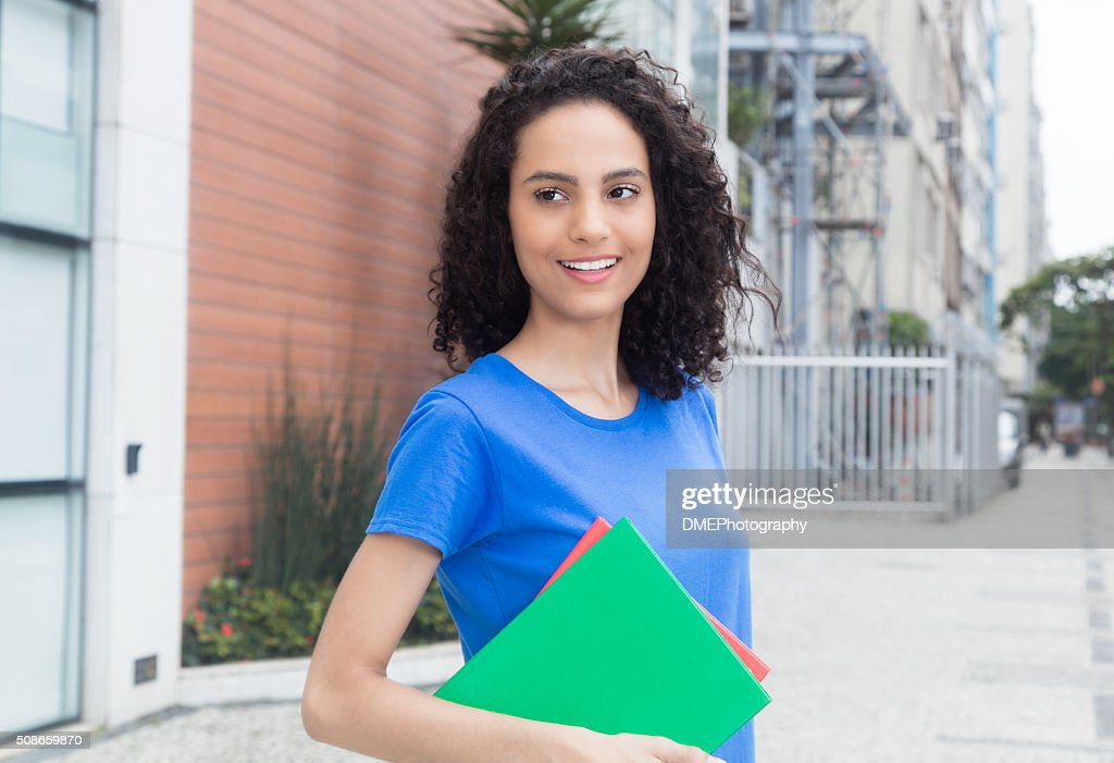 Happy caribbean student with books in the city : Stock Photo