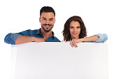 happy casual couple leaning elbows on blank board on white background