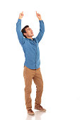 full body picture of a happy casual man celebrating victory with hands in the air on white background