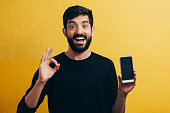 Happy casual man showing blank smartphone screen and ok sign over yellow background