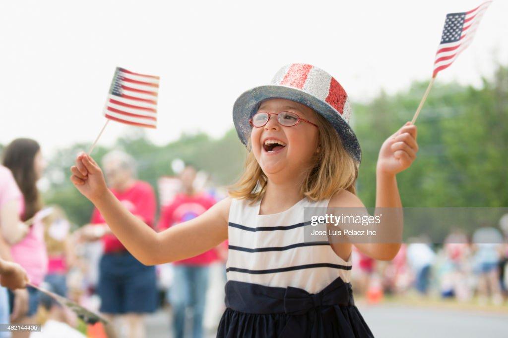 Happy Caucasian girl waving American flags at parade