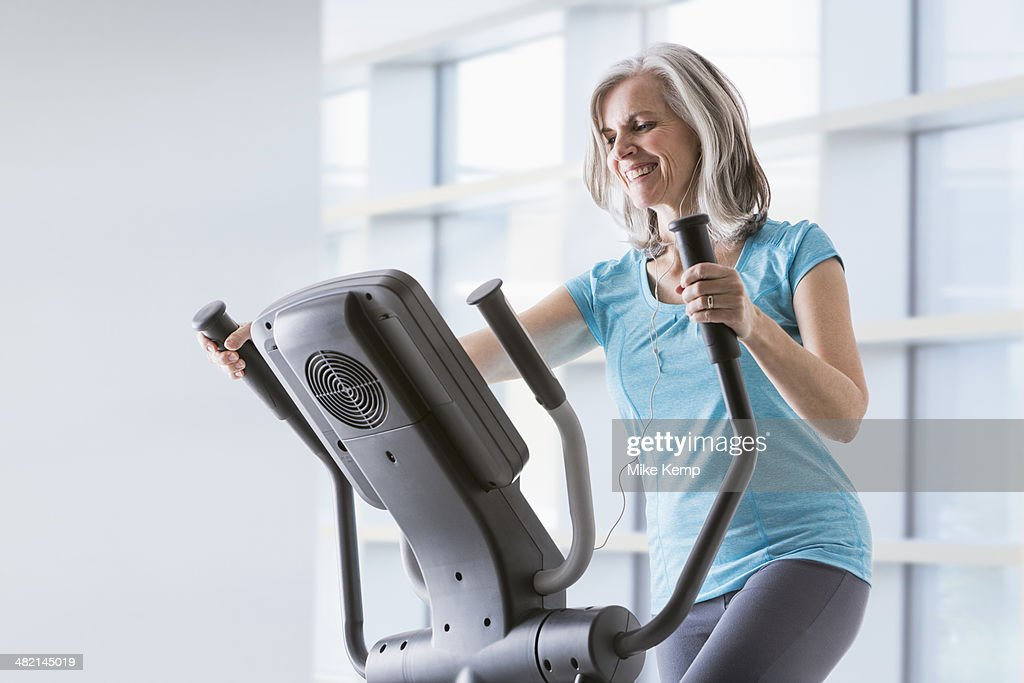 Happy Caucasian woman on elliptical trainer at gym
