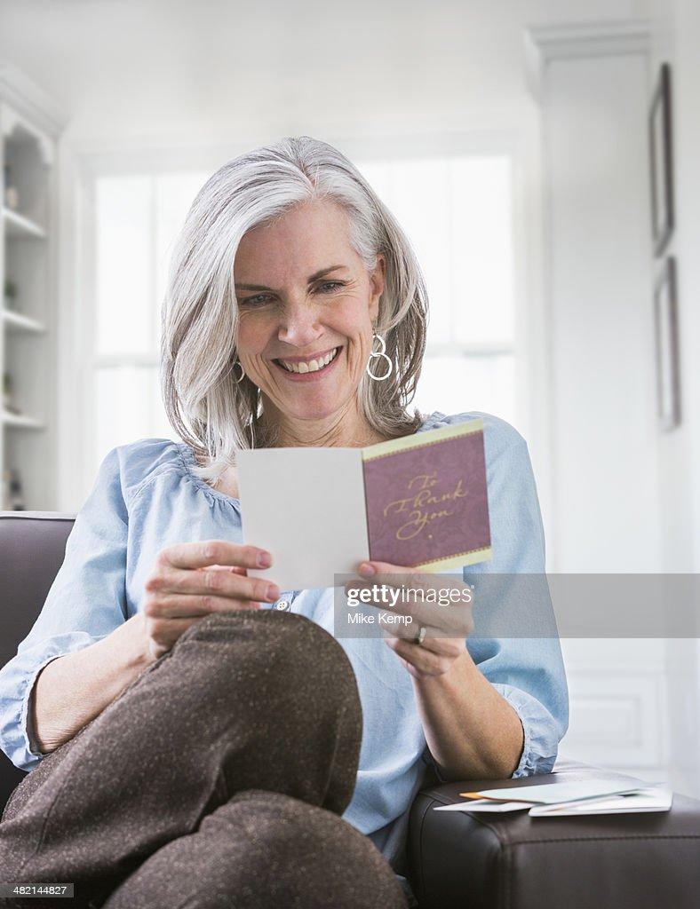 Happy Caucasian woman reading card on sofa