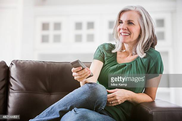 Happy Caucasian woman watching TV on sofa