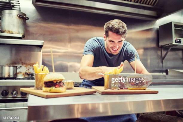 Happy chef arranging burger and French fries