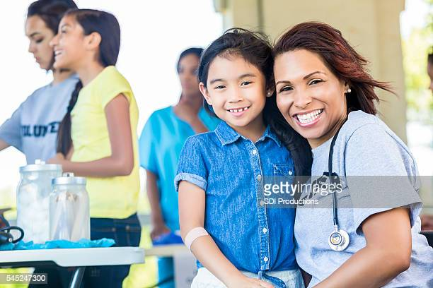 Happy child and medical volunteer hugging