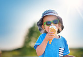 Happy child eating ice cream outdoors in summer. Portrait of a boy in sunglasses on sunny day