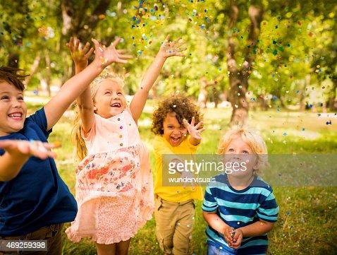 Happy child friends having fun with confetti in a park