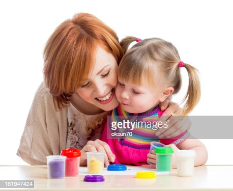 Happy child girl and mother playing with clay toy : Stock Photo