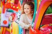 happy child girl riding train on funfair on summer vacationhappy child girl riding train on funfair on summer vacation
