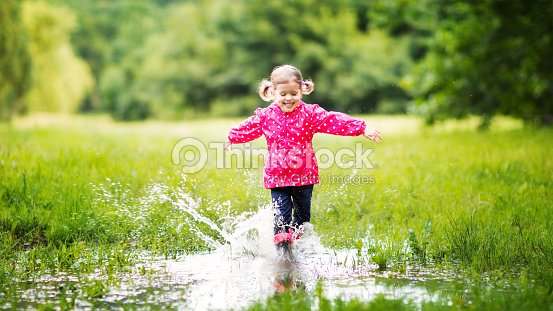 happy child girl running and jumping in puddles after rain ストック