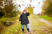 Cute toddler girl throws autumn leaves and laughs outdoors, fall day, walking in the park.