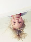 Happy child hanging upside down from bunk bed