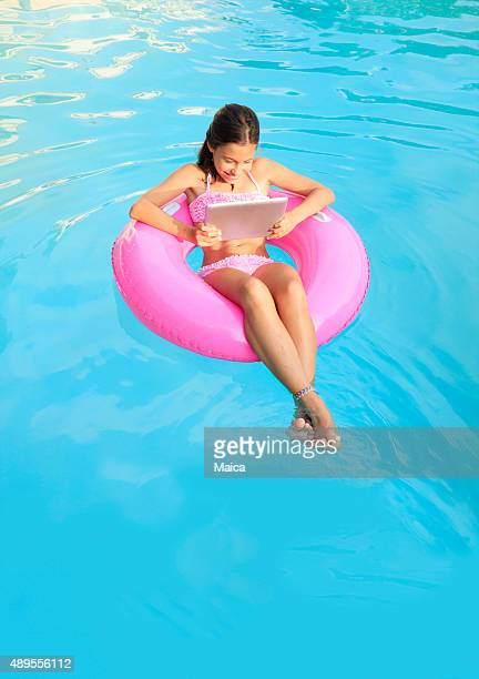 Happy child in the swimming pool with tablet