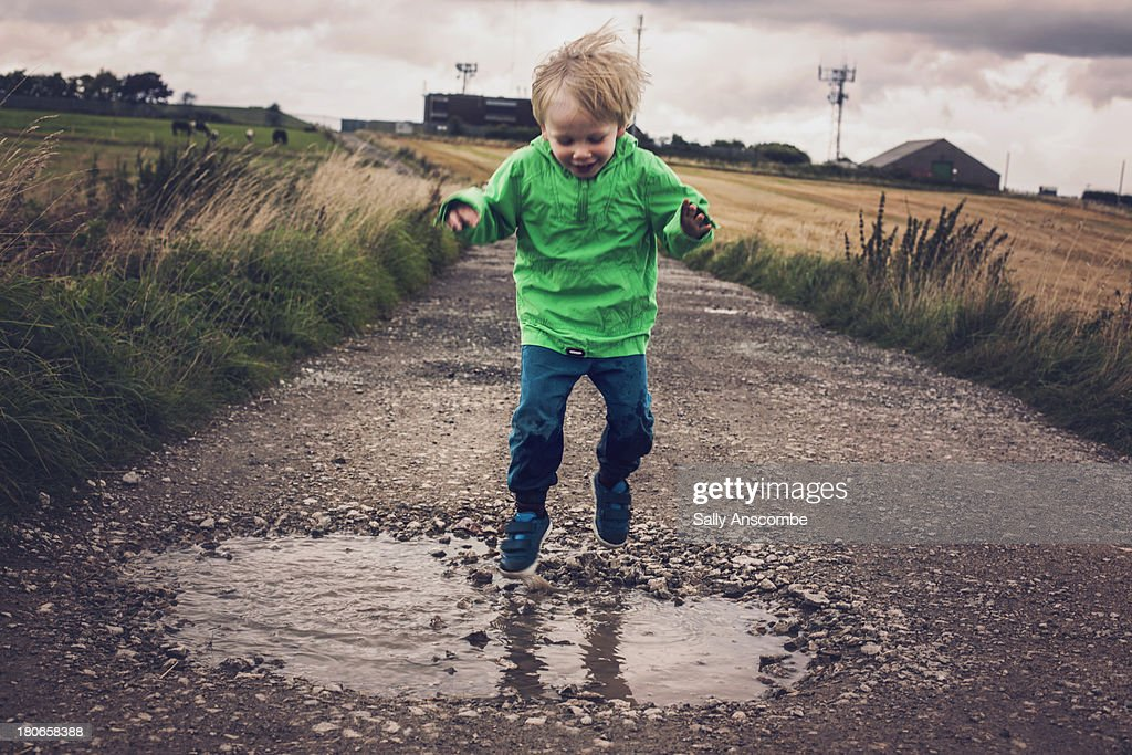 Happy child jumping in a puddle