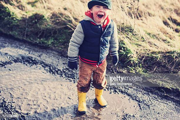 Happy child jumping in muddy puddles