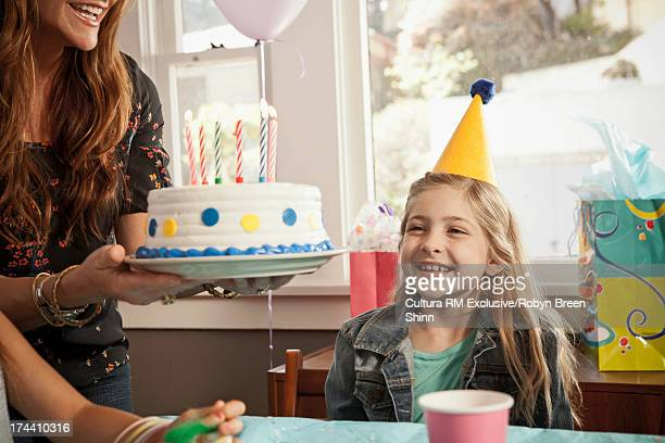 Happy child looking at birthday cake
