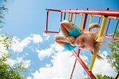 Low angle view of cute blond girl wearing blue tshirt hanging from a monkey bars. Girl is smiling with her eyes closed. The climbing frame is painted in red yellow green colors and located in the cour