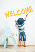 """Happy child paints with paint. The inscription on the wall """"Welcome"""""""