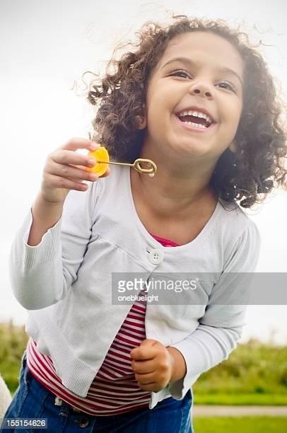 Heureux enfant (5-6) jouant avec des bulles de la robinetterie