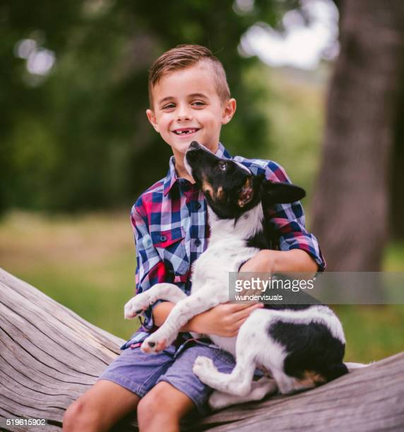 Glückliches Kind mit seinen Welpen Hund auf seinem Schoß