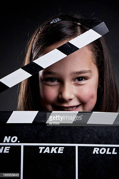 Happy child with movie clapper board.