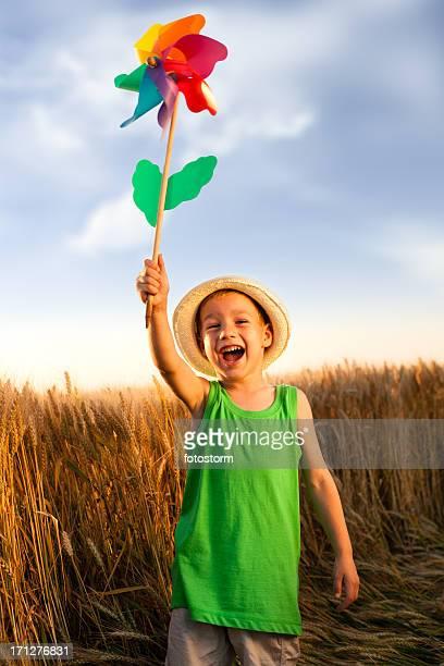 Enfant heureux sur le champ de blé avec moulin à vent
