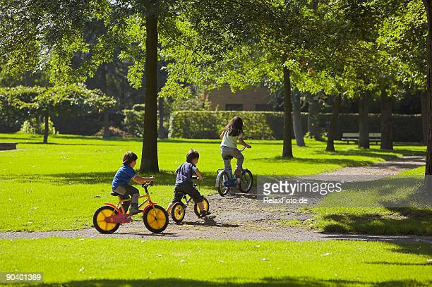 Happy childhood - Three Children cycling in park