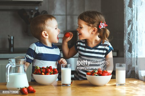 Happy children brother and sister eating strawberries with milk : Stock Photo