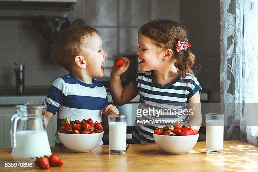 Glückliche Kinder-Bruder und Schwester, Essen Erdbeeren mit Milch : Stock-Foto