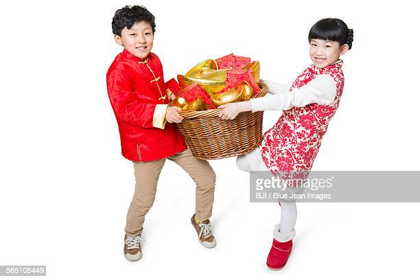 Happy children carrying red envelopes and Chinese traditional currency yuanbao