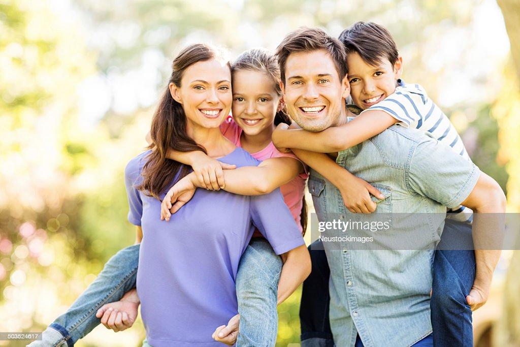 Happy Children Piggyback Ride disfrutar de sus padres : Foto de stock
