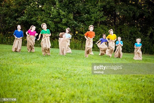 Happy Children Having a Fun Potato Sack Race Outside